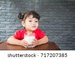 asian little girl drinking a... | Shutterstock . vector #717207385