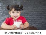 asian little girl drinking a... | Shutterstock . vector #717207445