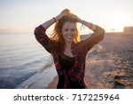 charming young woman walks on... | Shutterstock . vector #717225964