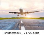 Small photo of Passenger airplane landing at sunset on a runway
