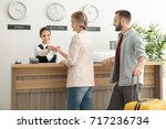 Stock photo young couple receiving key from hotel room at reception 717236734