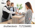 young woman near reception desk ... | Shutterstock . vector #717236881