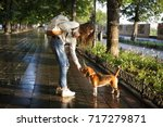 Stock photo full length side view image of young brunette woman in autumn clothes walks with dog in park 717279871
