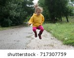 cheerful child jumping in a... | Shutterstock . vector #717307759