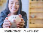 piggy bank in hand on wooden... | Shutterstock . vector #717343159