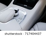 Stock photo media volume and navigation control buttons of a modern car car interior details white leather 717404437