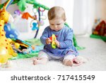 adorable baby girl playing with ... | Shutterstock . vector #717415549