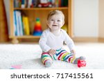 adorable baby girl playing with ... | Shutterstock . vector #717415561