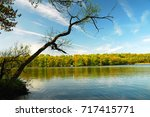 a lake reflects the summer sky... | Shutterstock . vector #717415771