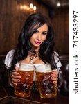 oktoberfest woman wearing a... | Shutterstock . vector #717433297