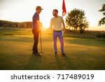 shot of two golfers shaking... | Shutterstock . vector #717489019