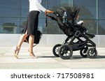 business mother pushing baby on ... | Shutterstock . vector #717508981