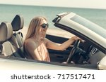 young woman drive a car on the... | Shutterstock . vector #717517471