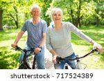 senior couple riding bikes in... | Shutterstock . vector #717524389
