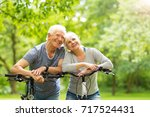 senior couple riding bikes in... | Shutterstock . vector #717524431
