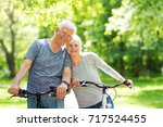 senior couple riding bikes in... | Shutterstock . vector #717524455