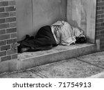 a homeless man bundled up under ...