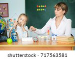 cute schoolgirl and her teacher ... | Shutterstock . vector #717563581