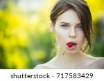 girl with cherry berry in mouth.... | Shutterstock . vector #717583429