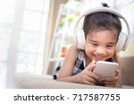 happy  asian girl using... | Shutterstock . vector #717587755