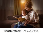 grandmother reading a tale to... | Shutterstock . vector #717610411
