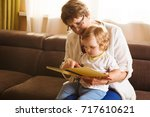 Small photo of Grandmother reading a tale to her baby granddaughter. Family Reading Leisure