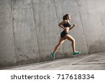 Small photo of Female sport runner striving into bright future. Fit body requires hard work. Urban sport concept.
