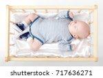 cute newborn baby in wooden bed | Shutterstock . vector #717636271