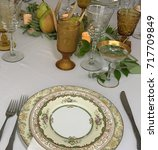Small photo of Fall luxury china place setting with pears, antlers, amber glass and gold rimmed champagne glasses for a family thanksgiving celebration.