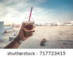 hand holding ice coffee in air... | Shutterstock . vector #717723415