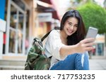 asia woman walking and using a... | Shutterstock . vector #717753235