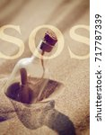 Small photo of A message in a bottle washed ashore. SOS - the word in the background