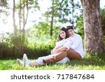 happy and young pregnant couple ... | Shutterstock . vector #717847684