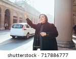young woman outdoor hailing a... | Shutterstock . vector #717886777