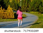 woman running in autumn park ... | Shutterstock . vector #717933289