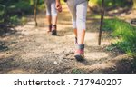Children hiking in mountains or forest with sport hiking shoes. Girls or boys are walking trough forest path wearing mountain boots and walking sticks. Frog perspective with focus on the shoes.