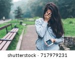 sad woman standing in the park... | Shutterstock . vector #717979231