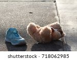 Small photo of 1 side of little girl shoe and her doll were left or fall off on the road.Nobody,girl was disappeared,only small blue shoe and doll are remain.Concept of missing and exploited children,lose child