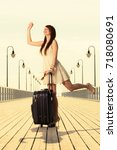 Small photo of Travel, packing, journey concept. Woman wearing white short dress standing next to her suitcase waving to somebody, pier in background.