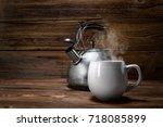 metallic teapot on a wooden... | Shutterstock . vector #718085899