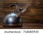 metallic teapot on a wooden... | Shutterstock . vector #718085935
