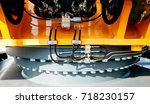 Small photo of Under the excavator - detail of the yellow swing drive and slewing ring of modern powerful excavator on a construction site
