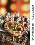 Small photo of Casino theme. High contrast image of casino roulette, poker game, dice game, poker chips on a gaming table, all on colorful bokeh background.