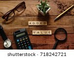 "Small photo of Top view wood text ""Added value"" with brown glasses,calculator,gold pen,black watch,magnifying glass and white pot plant.For Thinking Business Plan concept.Have copy space"
