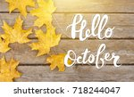 Golden autumn maple leaves on sunny day. Great season texture with fall mood. Nature september and october background with hand lettering Hello October.