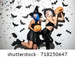 Small photo of Picture of two emotional young women in halloween costumes on party over white background with pumpkin. Looking aside.