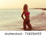 woman in bikini on beach   Shutterstock . vector #718256455