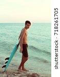 handsome surfer holding his...   Shutterstock . vector #718261705