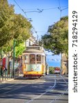 Small photo of Lisbon, Portugal - August 25, 2017: famous historic yellow Tram 28 on Alfama districts street. Scenic Tagus river on background. Trams are icon of the Portuguese capital. Lisbon urban views.