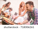 young family having barbecue... | Shutterstock . vector #718306261
